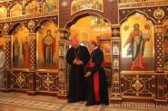Челли и Тадеуш Кондрусевич, беседуя, выходят ил алтаря храма в честь Всех Святых в Минске. 13 мая 2011 г.